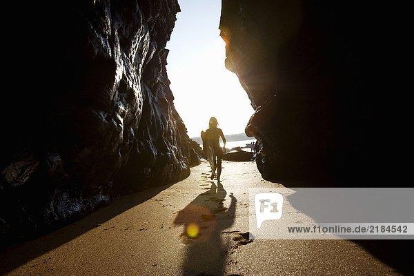 Frau trägt Surfbrett durch große Felsen.