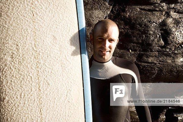 Mann steht mit lächelndem Surfbrett.