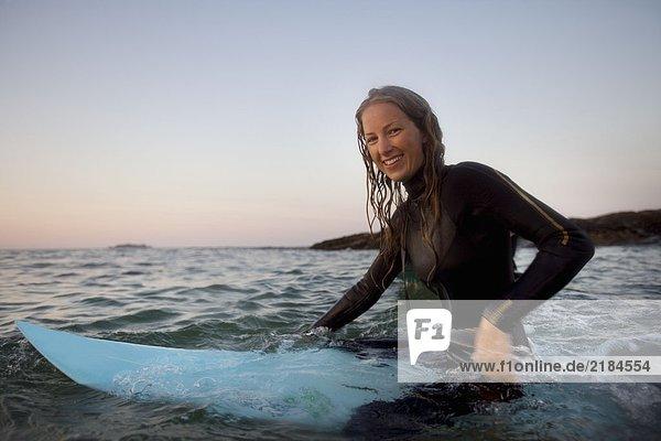 Frau sitzt auf dem Surfbrett im Wasser und lächelt.