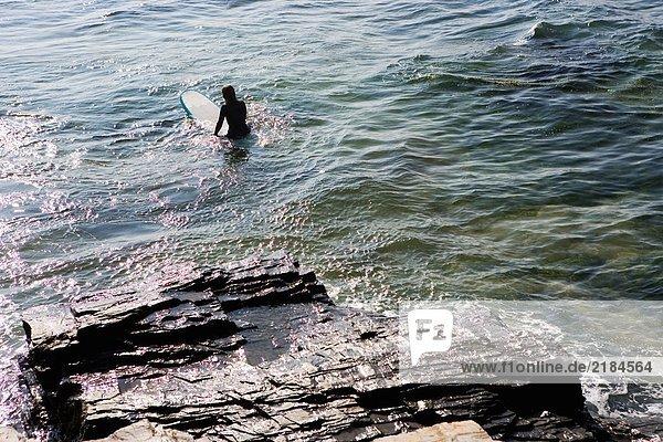 Frau sitzt auf dem Surfbrett im Wasser.