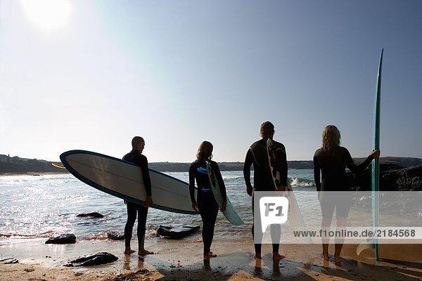 Vier Leute mit Surfbrettern am Strand.