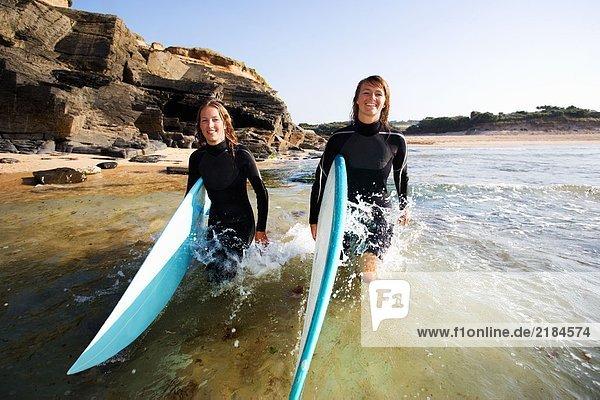 Zwei Frauen mit Surfbrettern im Wasser lächelnd.