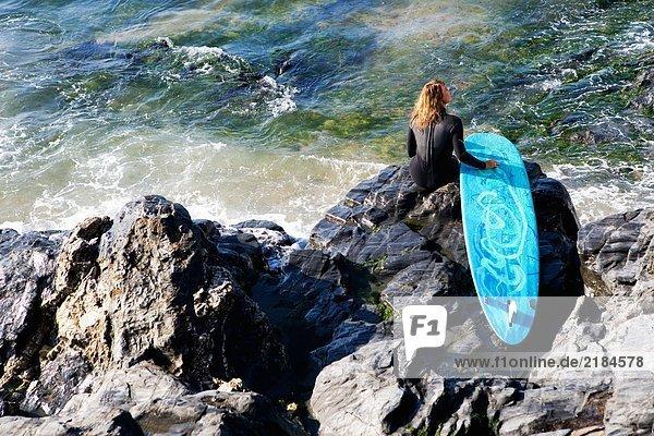 Frau sitzt mit einem Surfbrett auf großen Felsen.