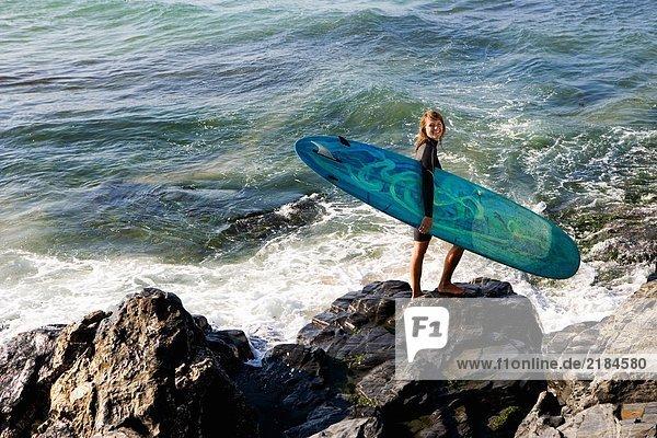 Frau auf großen Felsen stehend mit einem Surfbrett lächelnd.