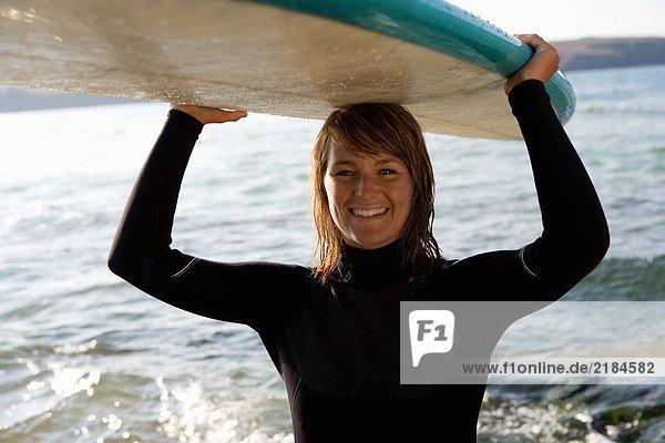 Frau steht mit einem Surfbrett über dem Kopf und lächelt.