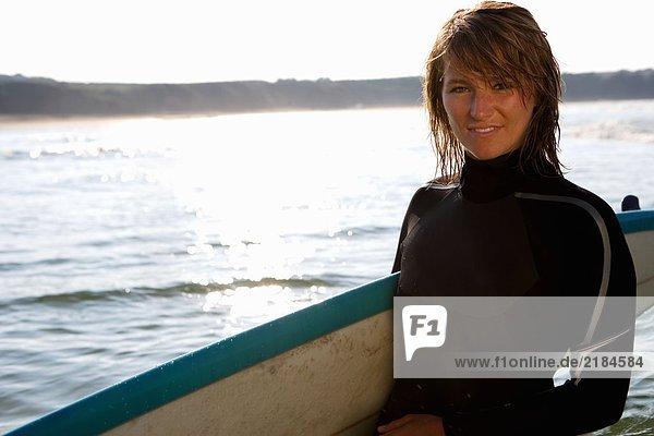 Frau steht mit einem Surfbrett.
