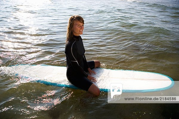 Frau sitzt auf einem Surfbrett und lächelt.