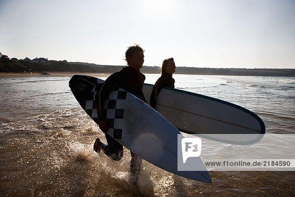 Ein Paar  das mit lächelnden Surfbrettern durchs Wasser läuft.