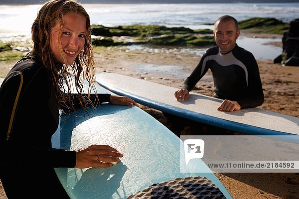 Paare  die ihre Surfbretter lächelnd wachsen.