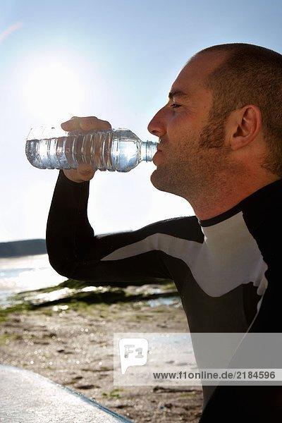 Mann sitzend mit Surfbrett Trinkwasser .