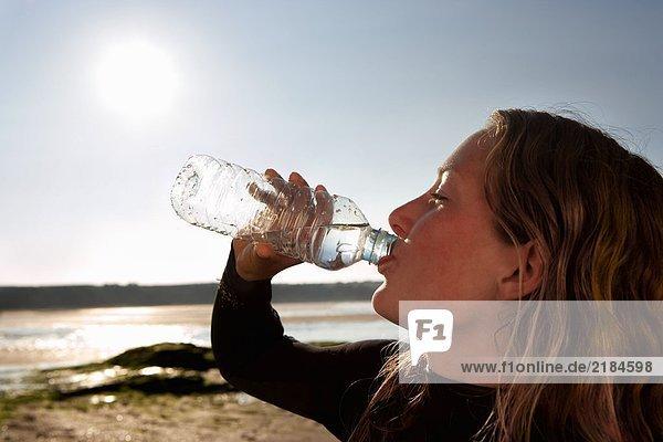 Frau trinkt Wasser im Neoprenanzug.