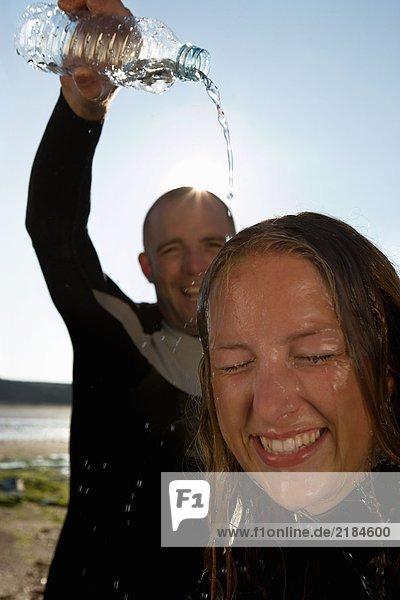 Lachender Mann  der Wasser über den Kopf der Frau gießt.
