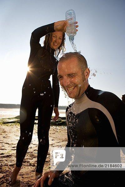 Frau gießt Wasser über den Kopf des lachenden Mannes.