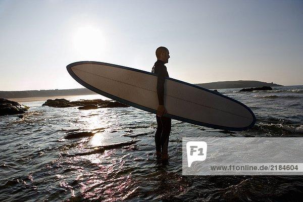 Mann steht im flachen Wasser mit Surfbrett.