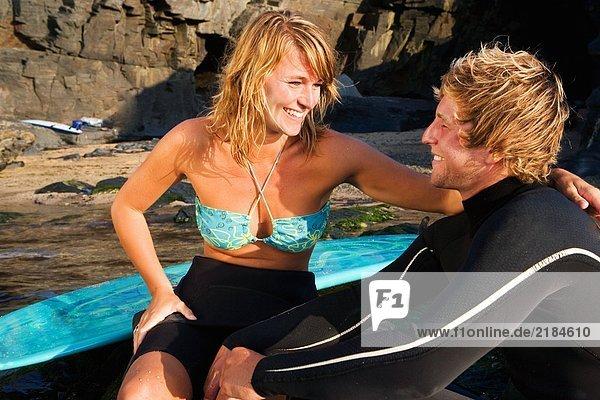 Paar auf großen Felsen sitzend mit lachenden Surfbrettern.