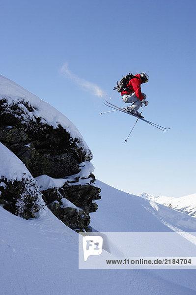 Österreich  Saalbach  Skispringen über Felsen auf verschneiter Piste