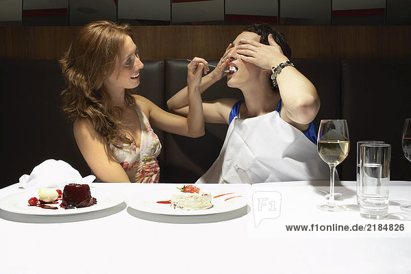 Two women in a restaurant feeding each other