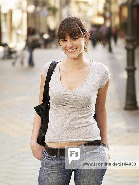 Junge Frau auf der Straße stehend  lächelnd  Portrait