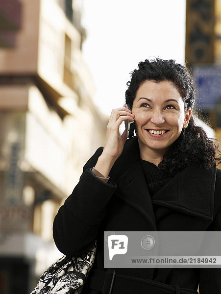 Woman standing in street using mobile phone  smiling