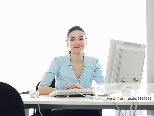 Junge Geschäftsfrau am Schreibtisch im Büro sitzend,  lächelnd,  Portrait