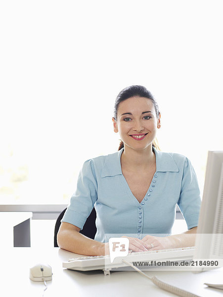 Junge Geschäftsfrau am Schreibtisch im Büro sitzend  lächelnd  Portrait