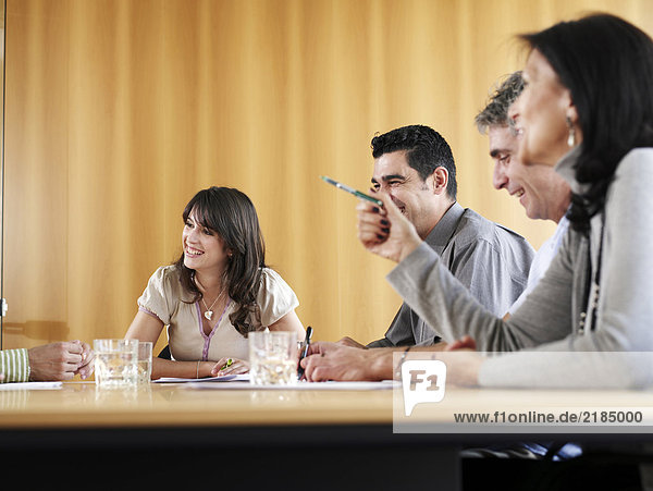 Young businesswoman in meeting with colleagues  smiling