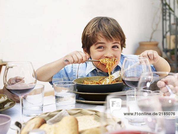 Junge (4-6) isst Spaghetti  lächelnd  Portrait