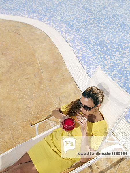 Frau entspannt auf Sonnenliege am Pool Frau entspannt auf Sonnenliege am Pool