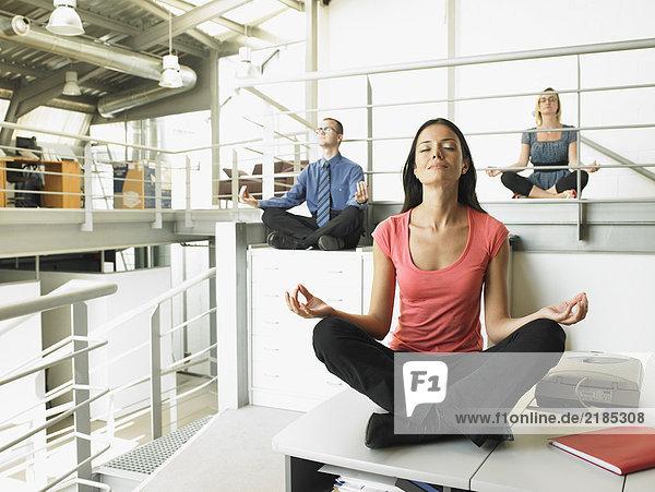 Junge Erwachsene sitzen auf Bürotischen in Yogaposition