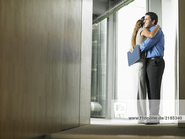 A woman hugging a man in a hallway