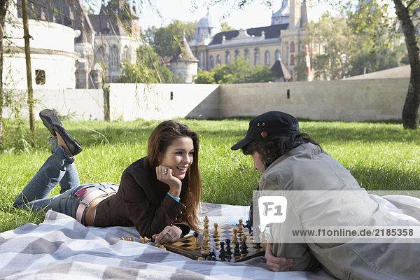 Ein Paar spielt Schach in einem Park und lächelt.