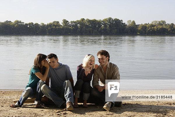 Vier Freunde sitzen auf einem Baumstamm am See und lächeln.