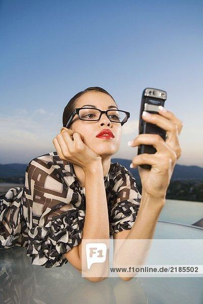 Frau  die sich auf den Tisch lehnt und das Handy im Freien betrachtet.