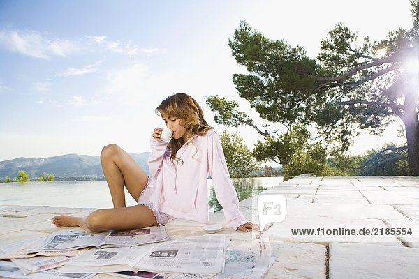Frau entspannt sich am Infinity-Pool und liest Zeitung und trinkt Kaffee.
