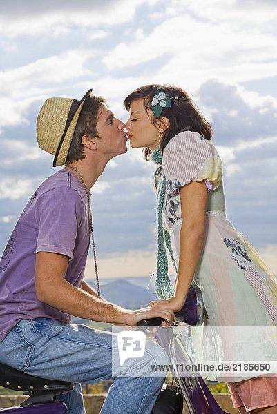 Frau küsst Mann auf Roller.