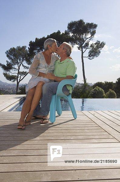 Ältere Paare umarmen sich auf der Terrasse.