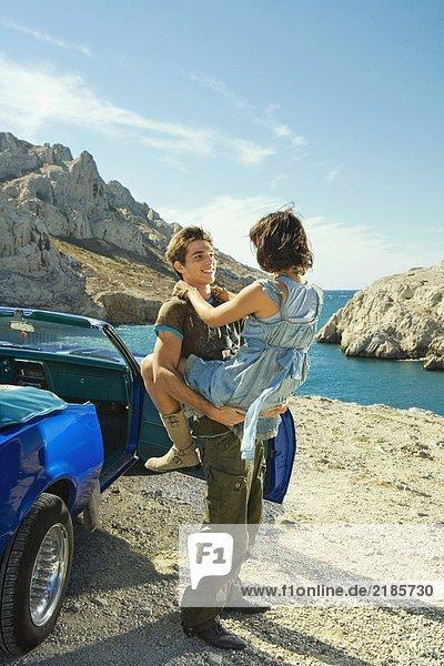Mann hält Frau mit dem Auto in der Luft.