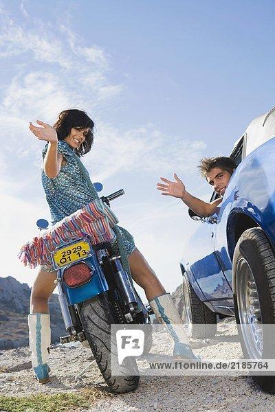 Mann im Auto Frau auf dem Motorrad.