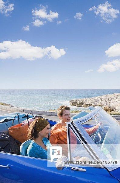Mann und Frau im Auto auf dem Seeweg.