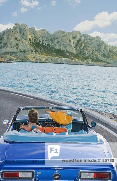 Mann und Frau fahren an der Küste vorbei.