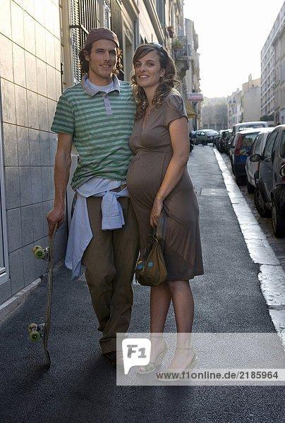 Schwangere junge Frau und junger Mann auf der Straße stehend  lächelnd  Portrait