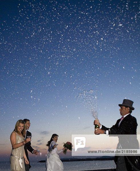 Mann öffnet Flasche Champagner über Hochzeitsfeier am Strand  Sonnenuntergang
