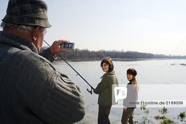 Großvater fotografiert Enkel (12-14) und Enkelin (10-12) beim Fischen im Fluss.
