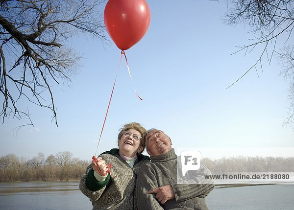 Seniorenpaar am Fluss mit rotem Ballon  lächelnd Seniorenpaar am Fluss mit rotem Ballon, lächelnd