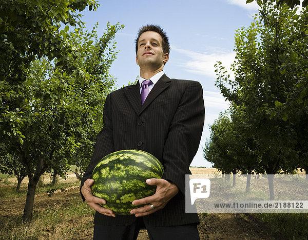 Mann mit Melone im Obstgarten.