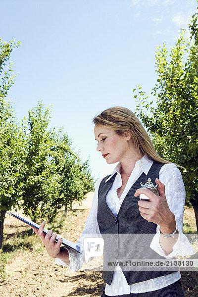 Frau mit Stoppuhr im Obstgarten.