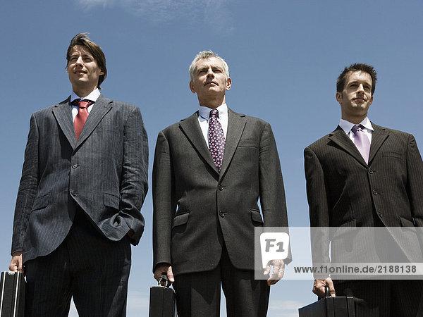 Drei Geschäftsleute stehen Seite an Seite.