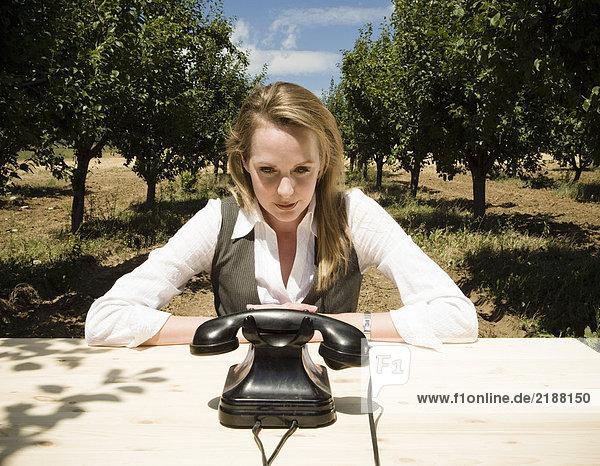 Frau sitzt am Schreibtisch mit altem Telefon im Obstgarten.