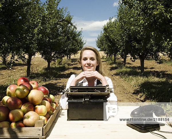 Frau sitzt am Schreibtisch im Obstgarten.