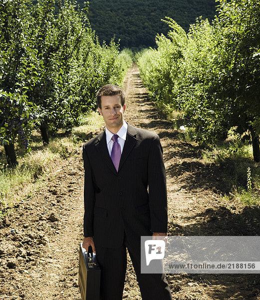 Mann stehend mit Aktentasche im Obstgarten.